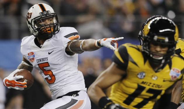 Oklahoma State wide receiver Josh Stewart (5) gestures on his way in for a touchdown against Oklahoma State during the first half of the Cotton Bowl NCAA college football game on Friday, Jan. 3, 2014, in Arlington, Texas. (AP Photo/Brandon Wade)