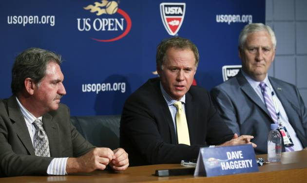 Patrick McEnroe, center, takes questions from reporters after he announced his resignation as the U.S. Tennis Association's general manager of player development at a news conference alongside David Haggerty, left, chairman, CEO and president of the USTA, and Gordon Smith, executive director and COO of the USTA, at the US Open, Wednesday, Sept. 3, 2014, in New York. (AP Photo/John Minchillo)