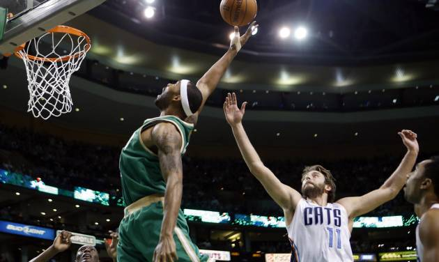Boston Celtics' Chris Wilcox, center left, reaches for a rebound in front of Charlotte Bobcats' Josh McRoberts (11) in the first quarter of an NBA basketball game in Boston, Saturday, March 16, 2013. (AP Photo/Michael Dwyer)