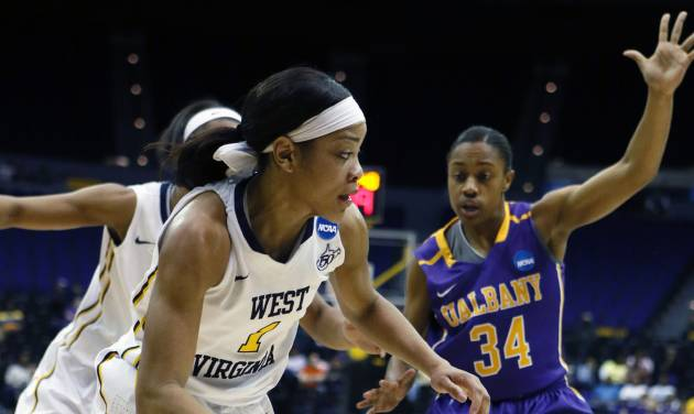 West Virginia guard Christal Caldwell (1) dribbles past Albany guard Cassandra Edwards (34) in the first half of an NCAA college basketball first-round tournament game on Sunday, March 23, 2014, in Baton Rouge, La. West Virginia won 76-61. (AP Photo/Rogelio V. Solis)