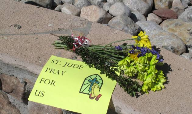A sign and flowers are left by a parishioner at the St. Jude Thaddeus Catholic Church in Albuquerque Monday, April 29, 2013, a day after a man stabbed several churchgoers Sunday as Mass was ending. Police say four parishioners were injured, including church choir director Adam Alvarez, but none have life-threatening injuries. Lawrence Capener, 24, is charged with three counts with aggravated battery and is being held on $75,000 bail.  (AP Photo/Russell Contreras)
