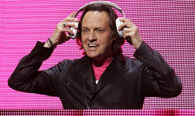 T-Mobile CEO John Legere puts on headphones as he announces a new music streaming service at T-Mobile's Uncarrier 5.0 event, Wednesday, June 18, 2014, in Seattle. (AP Photo/Ted S. Warren)