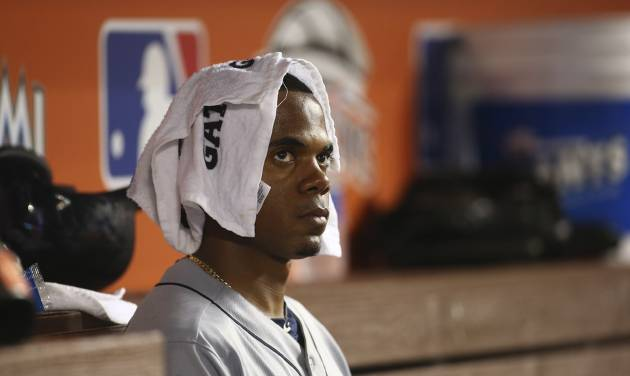 Seattle Mariners starting pitcher Roenis Elias sits in the dugout during the fifth inning of a baseball game against the Miami Marlins in Miami, Saturday, April 19, 2014. (AP Photo/J Pat Carter)