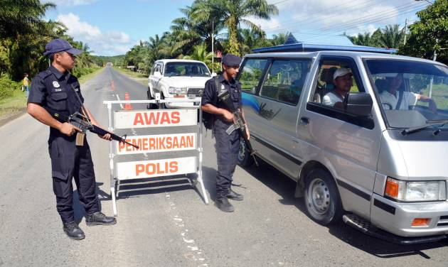 "Malaysian policemen check a vehicle along the main road near Lahad Datu in Malaysia's eastern Sabah state Thursday, Feb. 14, 2013. Malaysian security forces in Borneo surrounded armed intruders believed to be from the southern Philippines and sought to persuade them to leave peacefully Thursday, authorities said. The standoff has sparked one of the biggest security scares in recent years in Sabah, which is less than an hour by speedboat from southern Philippine provinces that have long been wracked by a Muslim separatist insurgency. The intruders landed in Sabah's largely rural, coastal district of Lahad Datu on Tuesday following ""troubles in the southern Philippines,"" national police chief Ismail Omar said. (AP Photo/Bernama News Agency) MALAYSIA OUT, NO SALES, NO ARCHIVE"