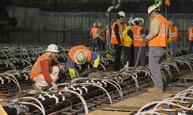 Crews pour concrete to lay the foundation for the New Wilshire Grand building in a record attempt for the largest continuous concrete pour in history, Saturday, Feb. 15, 2014, in downtown Los Angeles. The marathon pour is expected to last 20 hours without interruption. The attempt will be verified by an official from Guinness World Records. The New Wilshire Grand will be the tallest building to be built west of the Mississippi and is expected to be completed in 2017. (AP Photo/Mark J. Terrill)