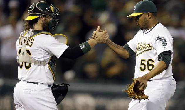 Oakland Athletics' Fernando Abad, right, celebrates with catcher Derek Norris after their 5-1 win in a baseball game against the Toronto Blue Jays Saturday, July 5, 2014, in Oakland, Calif. (AP Photo/Ben Margot)