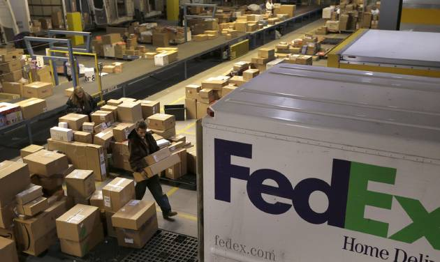 FILE - In this  Monday, Dec. 10, 2012, file photo, workers sort packages at a FedEx sorting facility in Kansas City, Mo. FedEx is more pessimistic about the U.S. economy than it was three months ago, but more assured of its own ability to grow earnings. The world's second-largest package delivery company lowered its economic forecast for the U.S., saying that there remains a lot of uncertainty for the company and the country. Its forecast for the current quarter, which incorporates the critical holiday season, falls short of Wall Street expectations. (AP Photo/Charlie Riedel, File)