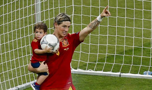 Spain's Fernando Torres holds his son Leo after an award ceremony as Spain won the Euro 2012 soccer championship final between Spain and Italy in Kiev, Ukraine, early Monday, July 2, 2012. (AP Photo/Vadim Ghirda)
