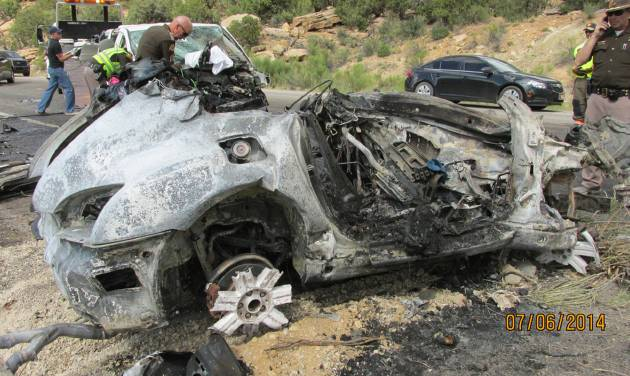 This photo provided by the Utah Department of Public Safety, shows a damaged vehicle from a head-on collision, Sunday July 6, 2014, in southern Utah.  A van carrying five people was trying to pass a vehicle on U.S. Route 191 when it struck an oncoming sports car holding two people near Monticello, about 285 miles southeast of Salt Lake City, the Utah Highway Patrol said.  Both people in the sports car died after it burst into flames, and three of the van's passengers were killed, Trooper Evan Kirby told KSL-TV. The other two passengers in the van were sent to the hospital in critical condition. (AP Photo/Utah Department of Public Safety)