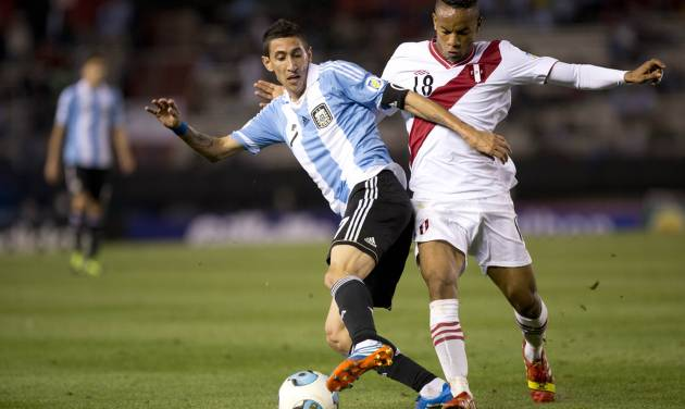 FILE - In this Oct. 11, 2013, file photo, Argentina's Angel Di Maria, left, vies for the ball with Peru's Andre Carrillo during a 2014 World Cup qualifying soccer match in Buenos Aires, Argentina. (AP Photo/Eduardo Di Baia)