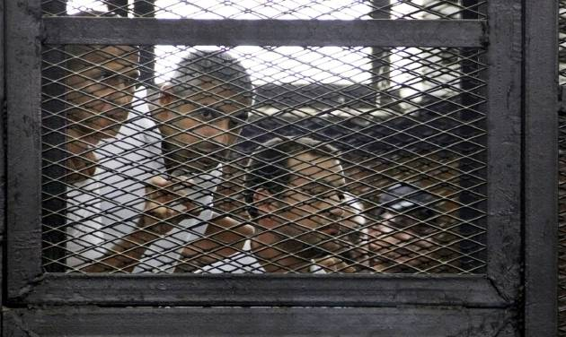 From left, Australian correspondent Peter Greste, Canadian-Egyptian acting bureau chief of Al-Jazeera Mohamed Fahmy, and Egyptian producer Baher Mohammed, appear in a defendant's cage in a courtroom in Cairo, Egypt, Monday, June 23, 2014. An Egyptian court on Monday convicted three journalists from Al-Jazeera English and sentenced them to seven years in prison each on terrorism-related charges, bringing widespread criticism that the verdict was a blow to freedom of expression. The three, Greste, Fahmy and Mohammed, have been detained since December charged with supporting the Muslim Brotherhood, which has been declared a terrorist organization, and of fabricating footage to undermine Egypt's national security and make it appear the country was facing civil war. (AP Photo/Heba Elkholy, El Shorouk Newspaper) EGYPT OUT