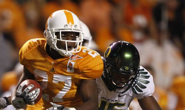 FILE - This Sept. 11, 2010 file photo shows Tennessee running back David Oku (27) carrying the ball as he's hit by Oregon linebacker Michael Clay (46) during an NCAA football game at Neyland Stadium in Knoxville, Tenn. Oku has signed with Arkansas State. ASU coach Gus Malzahn announced the signing of the former standout from Midwest City, Okla., on Wednesday, June 27, 2012. (AP Photo/Wade Payne, File)