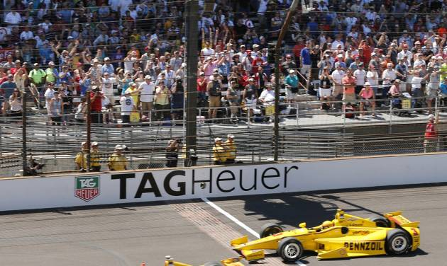 Ryan Hunter-Reay celebrates after crossing the finish line take the checkered flag in front of Helio Castroneves, of Brazil, to win the 98th running of the Indianapolis 500 IndyCar auto race at the Indianapolis Motor Speedway in Indianapolis, Sunday, May 25, 2014. (AP Photo/Dave Parker)