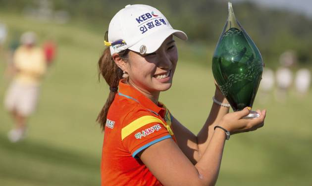 Hee Young Park, of South Korea, holds the trophy after winning the Manulife Financial LPGA Classic golf tournament on the third hole of a playoff, in Waterloo, Ontario, Sunday, July 14, 2013. (AP Photo/The Canadian Press, Geoff Robins)