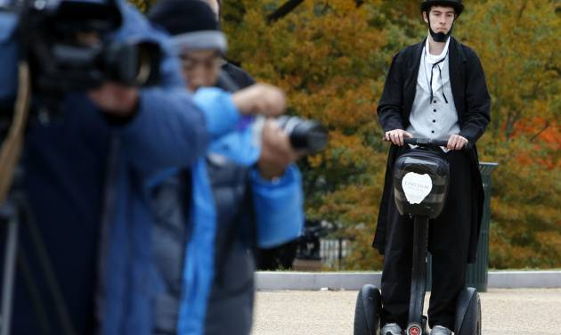 """As members of the media, left, wait, Christopher Brady, dressed as Abraham Lincoln, arrives on a Segway at the launching ceremony of the Lincoln Movie Trail at the State Capitol in Richmond, Va. Thursday, Nov. 15, 2012. With Steven Spielberg's """"Lincoln"""" set for national release Friday, Virginia tourism officials are inviting fans of history and film to tour the locations where the epic movie was made. (AP Photo/Richmond Times-Dispatch, Bob Brown)"""