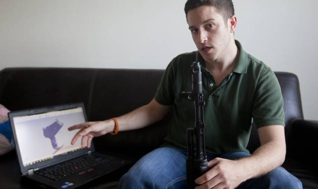 """In this Oct. 3, 2012 photo, """"Wiki Weapons"""" project leader Cody Wilson points to his laptop screen displaying an image of a prototype plastic gun on the screen, while holding in his other a weapon he calls """"Invivdual Mandate,"""" in Austin, Texas. At least one group, called Defense Distributed, is claiming to have created downloadable weapon parts that can be built using the increasingly popular new-generation of printer that utilizes plastics and other materials to create 3-D objects with moving parts. Wilson says the group last month test fired a semiautomatic AR-15 rifle _ one of the weapon types used in the Connecticut elementary school massacre _ which was built with some key parts created on a 3-D printer. The gun was fired six times before it broke. (AP Photo/Statesman.com, )  MAGS OUT; NO SALES; INTERNET AND TV MUST CREDIT PHOTOGRAPHER AND STATESMAN.COM"""