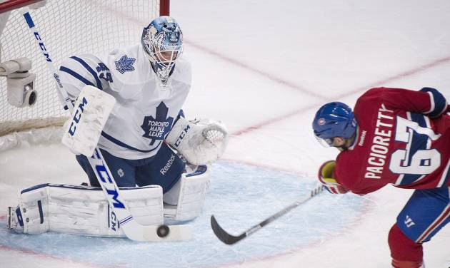 Toronto Maple Leafs goaltender Jonathan Bernier, left, makes a save against Montreal Canadiens' Max Pacioretty (67) during first-period NHL hockey game action in Montreal, Saturday, March 1, 2014. (AP Photo/The Canadian Press, Graham Hughes)