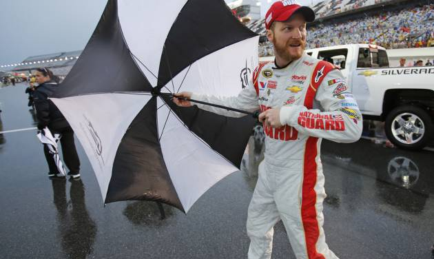 Dale Earnhardt Jr. opens his umbrella as he heads to the garages during a rain delay at the NASCAR Sprint cup Series auto race at Daytona International Speedway in Daytona Beach, Fla., Saturday, July 5, 2014. (AP Photo/Terry Renna)