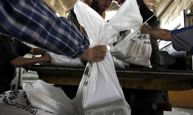 Workers fill a truck with bags depicting voting papers in Athens' municipality's warehouse, before delivering them to the polling stations around Athens, on Thursday, May 3, 2012. Greeks head to the polls in early general elections on May 6 .(AP Photo/Petros Giannakouris)