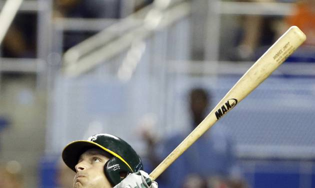 Oakland Athletics Nate Freiman watches the ball after he hit a three-run home run during the sixth inning of a baseball game, Sunday, June 29, 2014 in Miami. Josh Donaldson and Yoenis Cespedes scored on the play. The Athletics defeated the Marlins 4-3. (AP Photo/Wilfredo Lee)