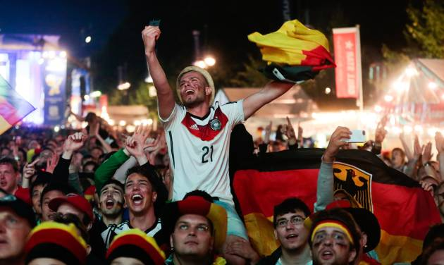 German fans react as they watch a live broadcast of the final match between Germany and Argentina at the soccer World Cup 2014 in Rio de Janeiro, Brazil, at a public viewing area called 'Fan Mile' in Berlin, Sunday, July 13, 2014. (AP Photo/Markus Schreiber)