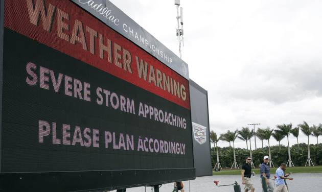 Spectators leave the golf course after play was suspended due to approaching inclement weather during the first round of the Cadillac Championship golf tournament, Thursday, March 6, 2014, in Doral, Fla. (AP Photo/Lynne Sladky)