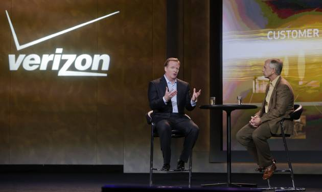 FILE - In this Jan. 8, 2013, file photo, NFL football commissioner Roger Goodell, left, and Verizon CEO Lowell McAdam talk about Verizon mobile products that allow NFL fans to watch games and interact with each other at the Consumer Electronics Show, in Las Vegas. The parent of the country's biggest wireless carrier lost $4.23 billion, or $1.48 per share, for the period ended Dec. 31. That compares with a loss of $2.02 billion or 71 cents per share, a year ago. (AP Photo/Julie Jacobson)