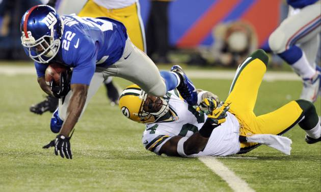 New York Giants' David Wilson (22) is tackled by Green Bay Packers' Jarrett Bush during the first half of an NFL football game, Sunday, Nov. 25, 2012, in East Rutherford, N.J. (AP Photo/Bill Kostroun)