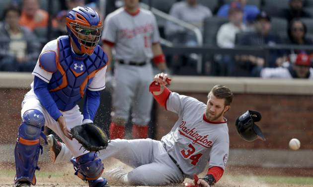 While New York Mets catcher Travis d'Arnaud, left, waits for the ball, Washington Nationals' Bryce Harper slides safely home during the seventh inning of the baseball game at Citi Field, Thursday, April 3, 2014 in New York. (AP Photo/Seth Wenig)
