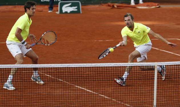 French pair Julien Benneteau, right, and Edouard Roger-Vasselin return the ball to Spanish pair Marcel Granollers and Marc Lopez during their final match of  the French Open tennis tournament at the Roland Garros stadium, in Paris, France, Saturday, June 7, 2014.  (AP Photo/Darko Vojinovic)