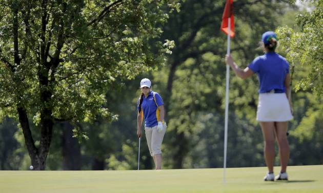 Katie Goodwin of Riverfield Country Day holds the pin flag as Mikera Morris of Dibble putts during the 2014 Class 2A girls' golf state championship tournament  Wednesday, May 7, 2014, at Trosper Golf Course in Del City.  Photo by Jim Beckel, The Oklahoman
