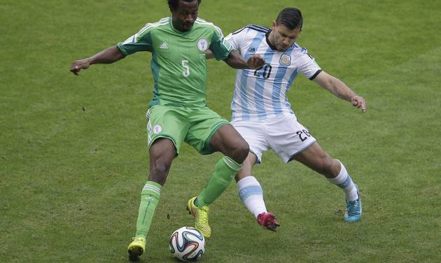 Nigeria's Efe Ambrose, left, and Argentina's Sergio Aguero battle for the ball during the group F World Cup soccer match between Nigeria and Argentina at the Estadio Beira-Rio in Porto Alegre, Brazil, Wednesday, June 25, 2014. (AP Photo/Michael Sohn)