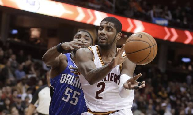 Cleveland Cavaliers' Kyrie Irving (2) passes the ball in front of Orlando Magic's E'Twaun Moore (55) during the second quarter of an NBA basketball game Wednesday, Feb. 19, 2014, in Cleveland. (AP Photo/Tony Dejak)