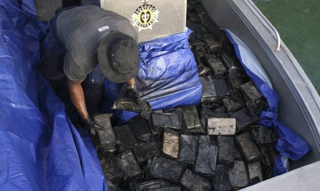 In this undated photo provided by the Australian Federal Police, an officer gathers packages of cocaine found on a yacht in Port Vila, Vanuatu. The 750 kilograms (1,650 pounds) of cocaine worth 370 million Australian dollars ($330 million) were found and seized on Monday, Aug. 19, 2013 after the U.S. Drug Enforcement Administration and Australian Federal Police collaborated with South Pacific governments, officials said Friday, Aug. 23, 2013. (AP Photo/Australian Federal Police) EDITORIAL USE ONLY