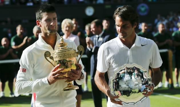 Serbia's Novak Djokovic, left, holds his trophy after defeating Switzerland's Roger Federer, right, in the men's singles final match at the All England Lawn Tennis Championships in Wimbledon, London, Sunday, July 6, 2014. (AP Photo/Ben Curtis)