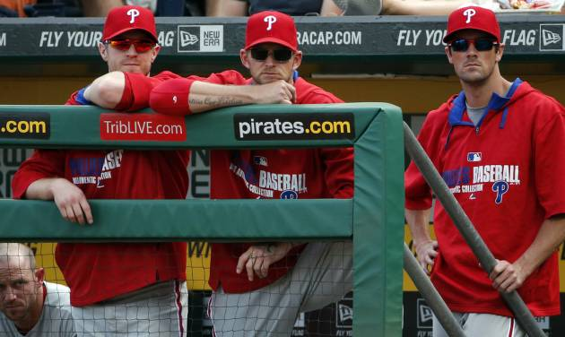 ADVANCE FOR USE SUNDAY, JULY 20 - FILE - In this July 5, 2014, file photo, Philadelphia Phillies starting pitchers A.J. Burnett, center, Kyle Kendrick, left, and Cole Hamels, right, stand in the dugout during the ninth inning of a baseball game against the Pittsburgh Pirates in Pittsburgh.  The Phillies are less than three years removed from a dominant run of five straight NL East titles, two pennants and one World Series championship. Despite having the highest payroll in franchise history, they are headed toward another last-place finish. (AP Photo/Gene J. Puskar, File)