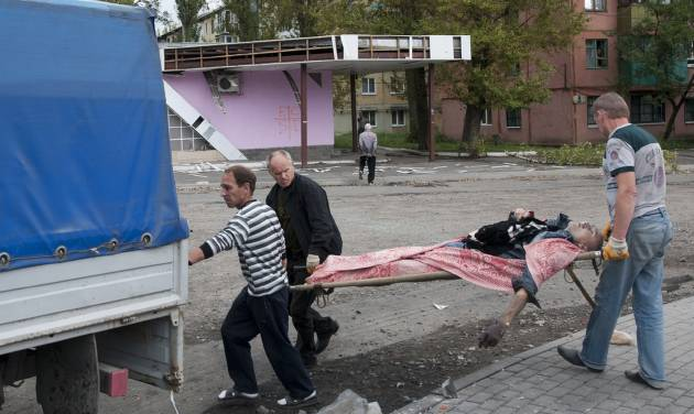 People carry a stretcher with a dead man after shelling by the Ukrainian forces in Makiivka, 25 km (16 miles) from Donetsk, eastern Ukraine, Tuesday, Aug. 19, 2014.  Government troops on Tuesday pressed attacks in the two largest cities held by pro-Russian rebels in eastern Ukraine, as Kiev also pursued diplomatic efforts to resolve the conflict that has killed more than 2,000. (AP Photo/Antoine E.R. Delaunay)