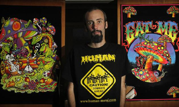 "In this photo taken April 30, 2012, Dave Snell of New Zealand stands in front of what he calls bogan art in Hamilton, New Zealand. Snell graduated from Waikato University in Hamilton on Thursday, May 3, 2012, with a doctoral degree that examined the social habits of headbangers - heavy-metal music fans that are known as ""bogans"" in this part of the world. Along the way, the New Zealander got an education in media and politics, after some people publicly derided a grant he received as an example of academic and taxpayer waste. (AP Photo/New Zealand Herald, Christine Cornege) NEW ZEALAND OUT, AUSTRALIA OUT"