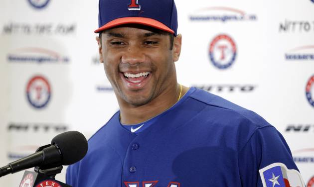 Seattle Seahawks quarterback Russell Wilson responds to a question during a news conference after a full day's workout with the Texas Rangers during spring training baseball practice, Monday, March 3, 2014, in Surprise, Ariz. (AP Photo/Tony Gutierrez)