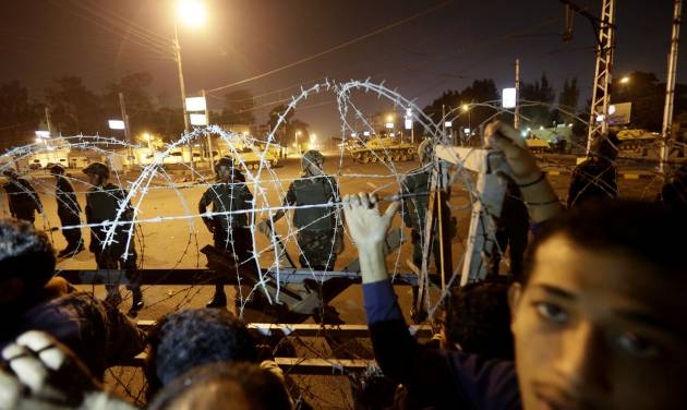 Egyptian protesters stand behind barbed wire on a road leading to the presidential palace during a protest against Egyptian President Mohammed Morsi, in Cairo, Egypt, Thursday, Dec. 6, 2012. The Egyptian army has deployed tanks outside the presidential palace in Cairo following clashes between supporters and opponents of Mohammed Morsi that left several people dead and hundreds wounded. (AP Photo/Hassan Ammar)