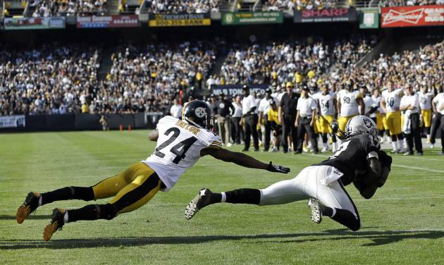Oakland Raiders wide receiver Denarius Moore, right, scores a touchdown on a six-yard pass as Pittsburgh Steelers cornerback Ike Taylor, left, looks on during the fourth quarter of an NFL football game in Oakland, Calif., Sunday, Sept. 23, 2012. Oakland won 34-31. (AP Photo/Marcio Jose Sanchez)