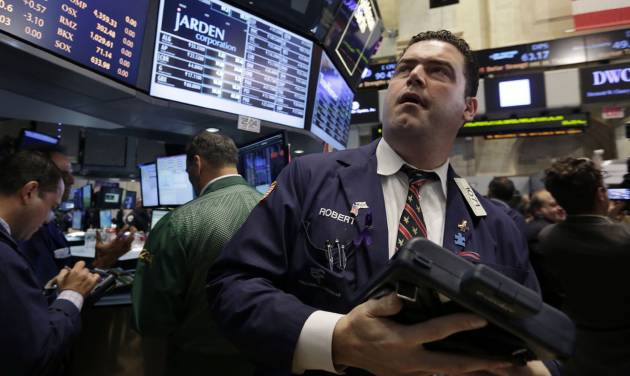 Trader Robert McQuade works on the floor of the New York Stock Exchange, Friday, June 20, 2014. Stocks are slightly higher in early trading as the market heads for a week of solid gains. (AP Photo/Richard Drew)