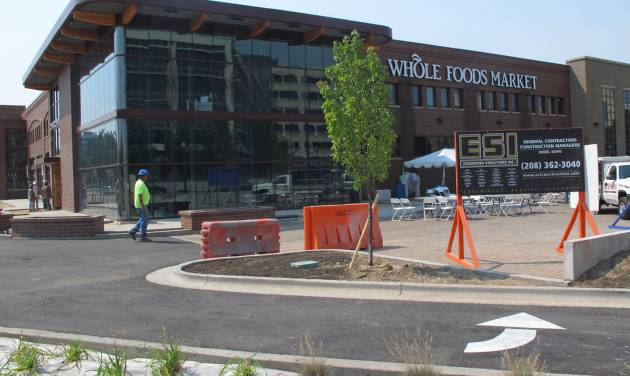 In a photo made Wednesday Aug. 29, 2012, construction workers finish the parking lot of the soon-to-open Whole Foods Market in Boise, Idaho. Across the country, aggressive expansion plans by Whole Foods and specialty grocer Trader Joe's, among others, are forcing independent food co-ops, the cradle of the organic retail trade, with roots dating back to the 1970s, to make changes to stay relevant. (AP Photo/John Miller).