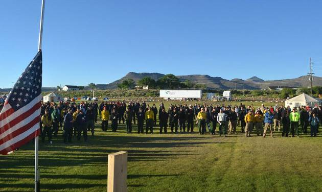 "In a photo provided by the Rio Grande National Forest, firefighting personnel at the West Fork Complex Incident Command in Del Norte, Colo., observe a moment of silence early Monday morning, July 1, 2013, for fellow firefighters killed Sunday fighting a wildfire in Yarnell, Ariz.  The out-of-control blaze killed 19 firefighters, nearly all of them members of an elite crew of ""hotshots,"" authorities said Monday. It was the nation's biggest loss of firefighters in a wildfire in 80 years. (AP Photo/Rio Grande National Forest, West Fork Complex, Andy Lyon)"