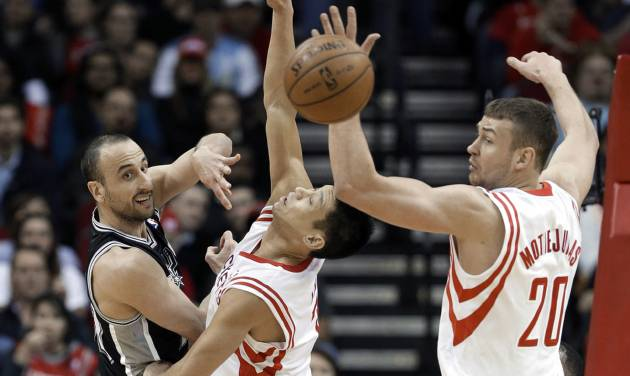 San Antonio Spurs' Manu Ginobili, left, passes the ball past Houston Rockets Jeremy Lin, center, and Donatas Motiejunas (20) during the first half of an NBA basketball game Tuesday, Jan. 28, 2014, in Houston. (AP Photo/Pat Sullivan)