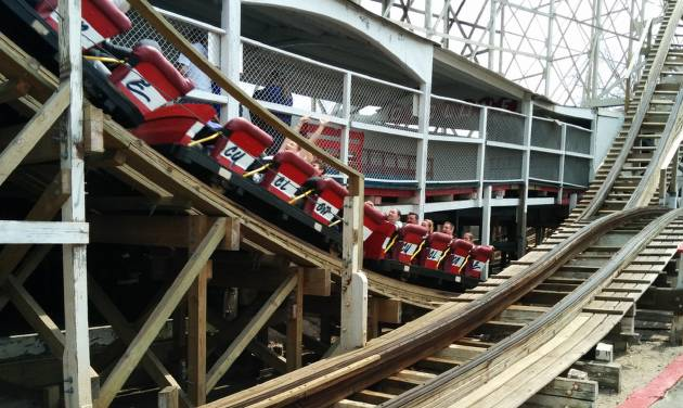 Visitors to Coney Island ride the Cyclone  at Luna Park in the Brooklyn borough of New York Sunday, April 13, 2014. The rides of Coney Island opened for another season with the 1920s wooden roller-coaster being christened with a dousing of a traditional egg cream drink. It marked the opening of the 40 rides of Luna Park, where 750 local residents are employed. (AP Photo/Julie Walker)