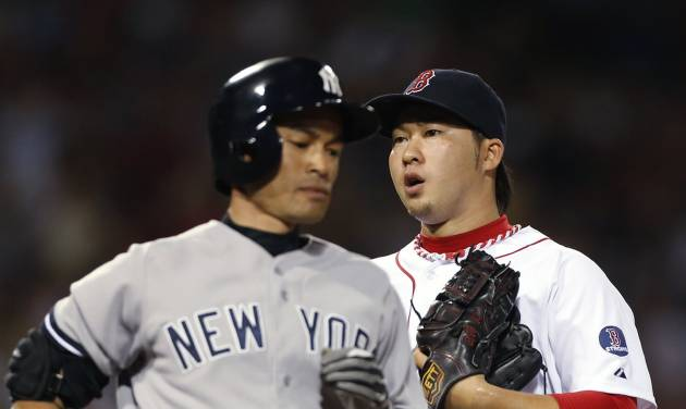 New York Yankees' Ichiro Suzuki, left, passes Boston Red Sox's Junichi Tazawa after grounding out to end the top of the seventh inning of a baseball game in Boston, Sunday, July 21, 2013. (AP Photo/Michael Dwyer)