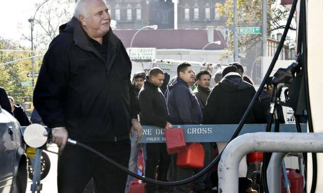 A motorist pumps gas while people stand in line with containers to purchase gas on Friday, Nov. 9, 2012 in Brooklyn, N.Y. Police were at gas stations to enforce a new gasoline rationing plan that lets motorists fill up every other day that started in New York on Friday morning. (AP Photo/Bebeto Matthews)