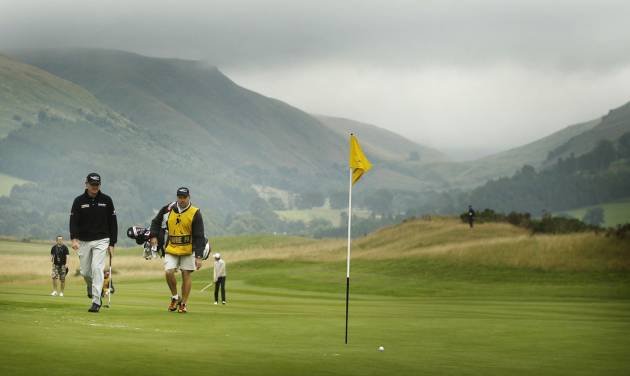 Paul Lawrie, left, walks towards his ball on a green during day one of the 2013 Johnnie Walker Championships at Gleneagles, Scotland Thursday Aug. 22, 2013. (AP Photo/Danny Lawson/PA) UNITED KINGDOM OUT