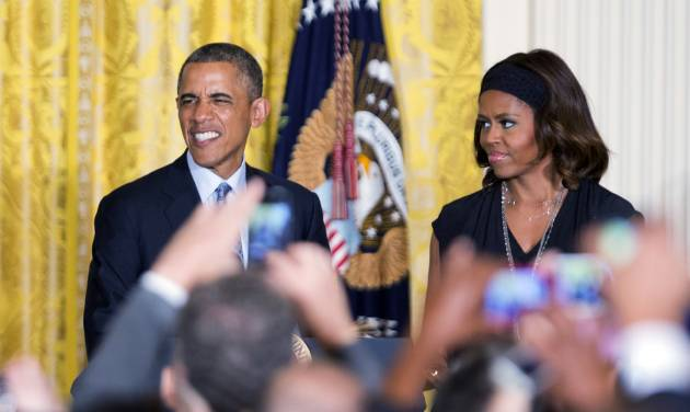 President Barack Obama, left, with first lady Michelle Obama, speaks during a reception to observe LGBT Pride Month in the East Room of the White House in Washington, Monday, June 30, 2014.    (AP Photo/Manuel Balce Ceneta)